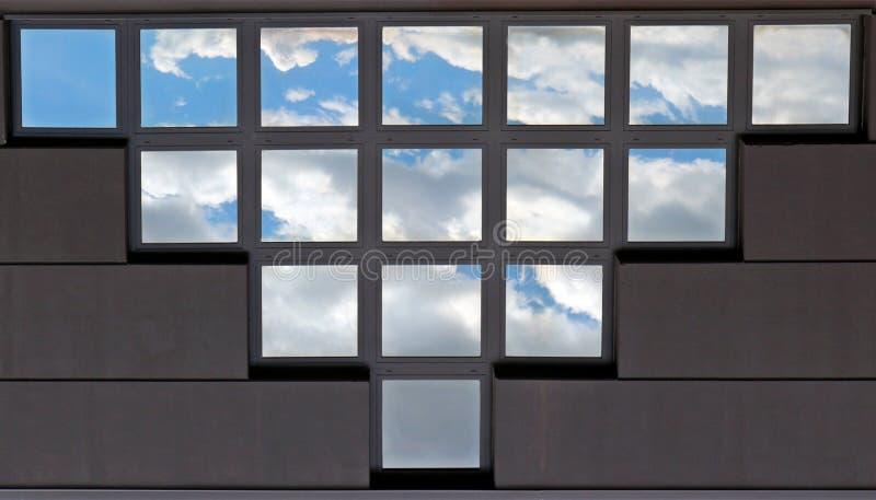 Detalj av en modern fasad med ett stort triangulärt fönster som utgöras av små fyrkanter som reflekterar himlen Bakgrund och text arkivbilder
