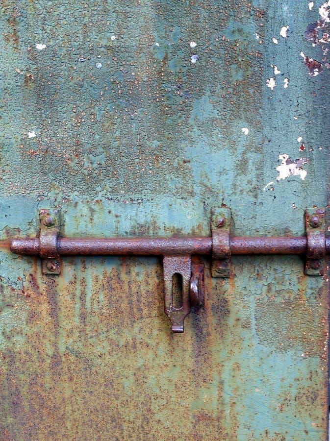 Detalj av en rostad dörr med tjockt stål som låser bulten arkivfoton