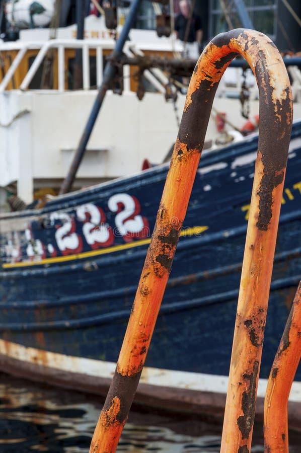 Detalj av en rostig ledstång med en fiskebåt på bakgrunden i byn av Ullapool i Skotska högländerna i Skottland som förenas royaltyfri bild