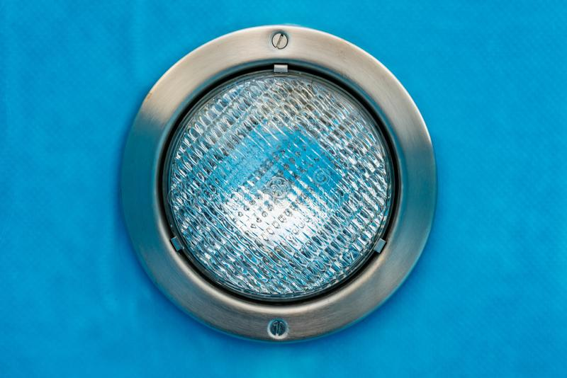 Detalj av en rund pölstrålkastare med blå bakgrund arkivbilder