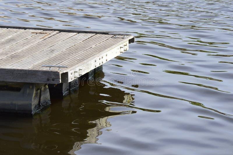 Detalj av en träpir i mörkt vatten Träskeppsdockadetalj fotografering för bildbyråer