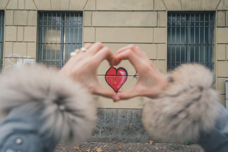 Detalj av en ung kvinna som gör en hjärta med henne fingrar arkivfoton