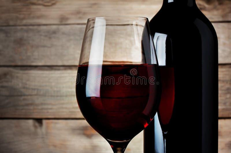 Detalj av ett glass rött vin med en flaska arkivbilder