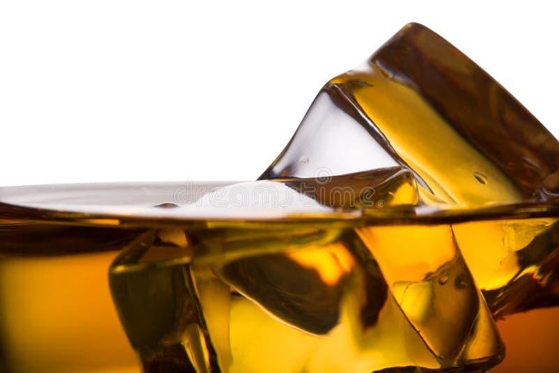 Detalj av ett whiskyexponeringsglas med is arkivfoton