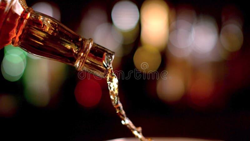 Detalj av hällande whisky för flaska royaltyfri foto