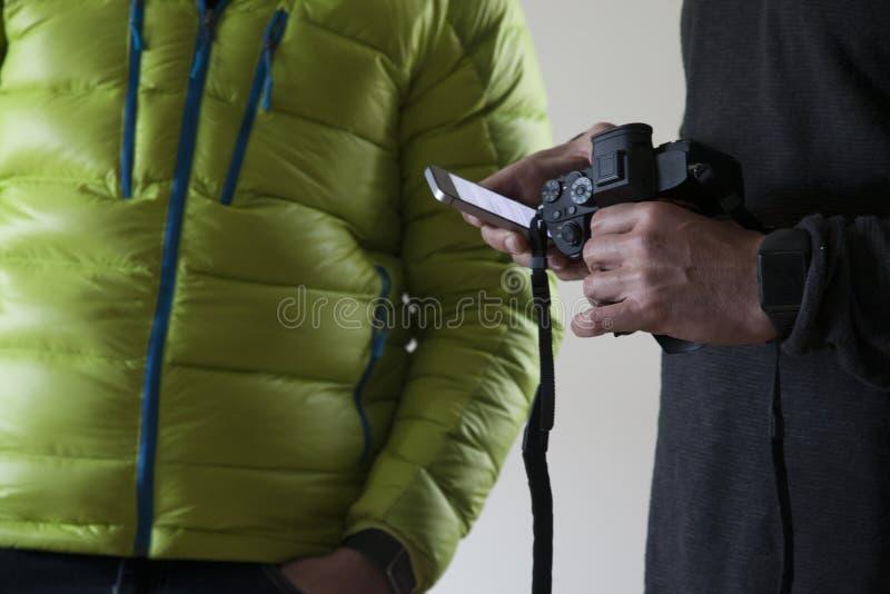 Detalj av händerna av en vit man som rymmer en av hans händer med en kamera och med annan hans mobiltelefon royaltyfri bild