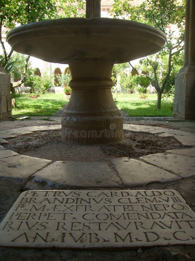 Detalj av handstilar i latin som inristas i en sten med bak en tabell av marmor i kloster av abbotskloster av Fossanova i Italien arkivfoton