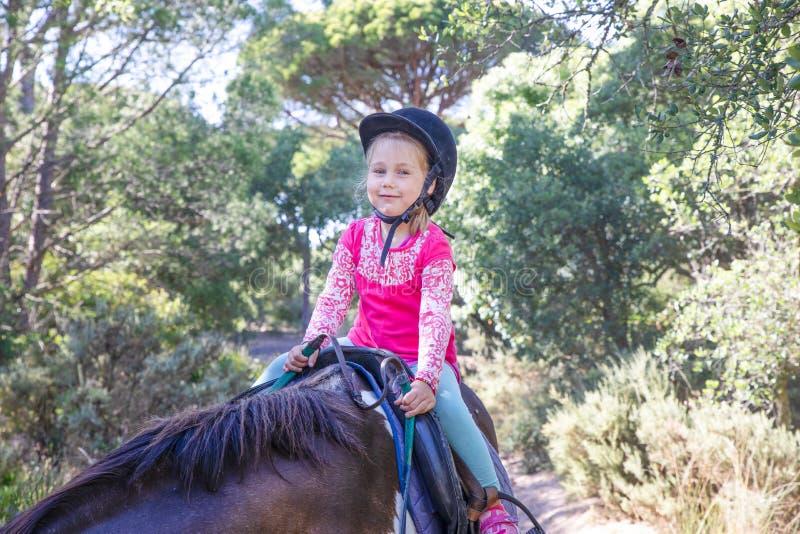 Detalj av lilla flickan som rider en häst i se för en skog och smi fotografering för bildbyråer