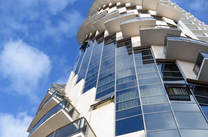 Detalj av modern stads- arkitektur - byggnaden på bakgrund för blå himmel av betong och exponeringsglas med balkongen som lokalis arkivbild