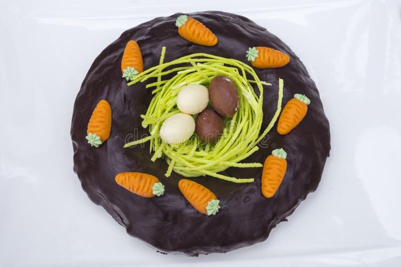 Detalj av påskchokladkakan med redet och söta ägg i vit bakgrund royaltyfria foton