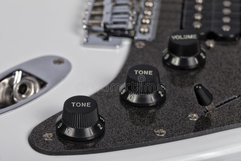 Detalj av potentiometrarna av en vit elektrisk gitarr royaltyfri foto