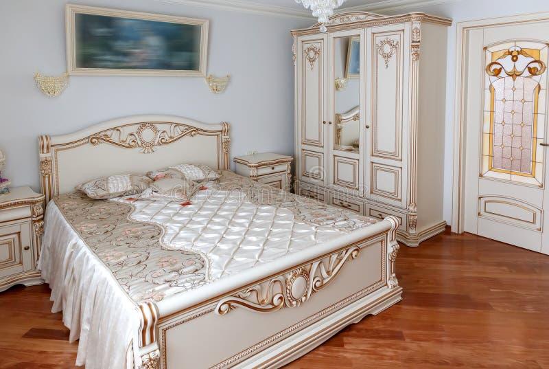 Detalj av sovrummet säng och nattduksbord som dekoreras med handgjorda carvings Möblemang i klassisk stil vitt träd med guld- t royaltyfri bild