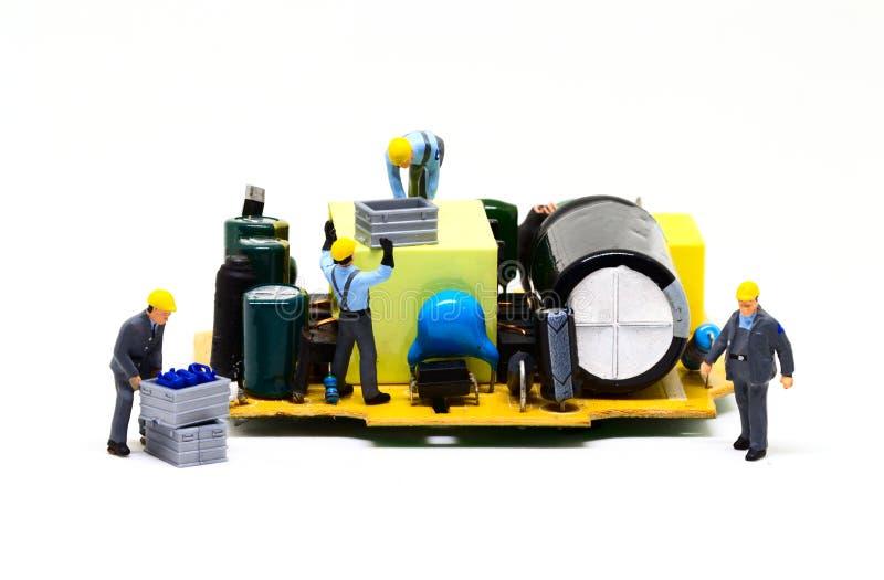 Detalj för arbetarreparationsdator Miniatyrarbetarstatyett och mikrochip Män på arbetsmakrofotoet royaltyfri fotografi