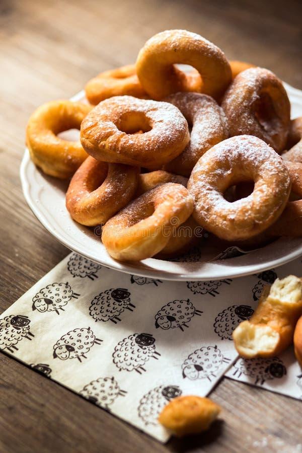 Detalj för bästa sikt på en grupp av nya hemlagade donuts (munkar) på en vit platta, med sockerbunken, kavel arkivfoto