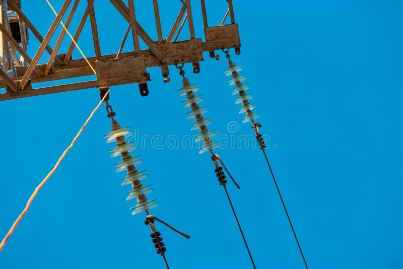 Detalj för makttorn med tre isolatorer för radod-exponeringsglas och trådarna arkivbild
