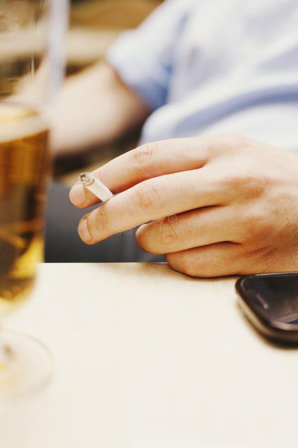 Detalj i ett kafé, hand som rymmer en cigarett royaltyfri fotografi
