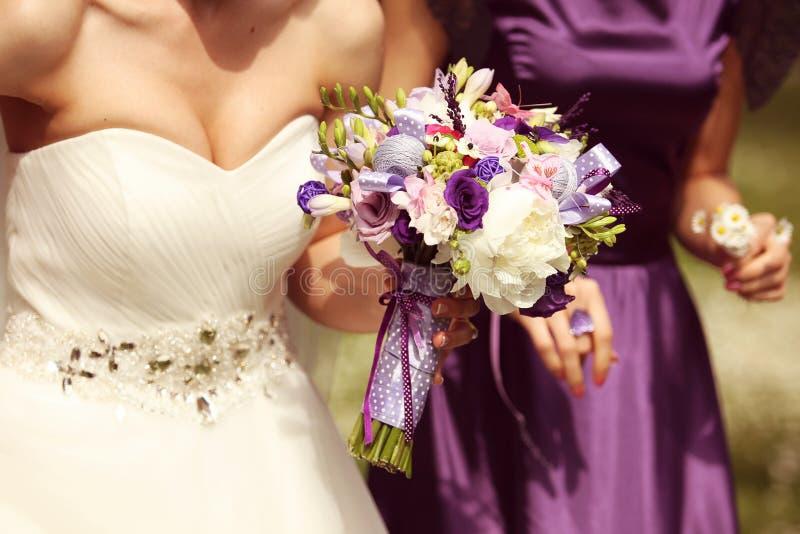 Detalj och brud och brudtärna med blommor royaltyfria bilder