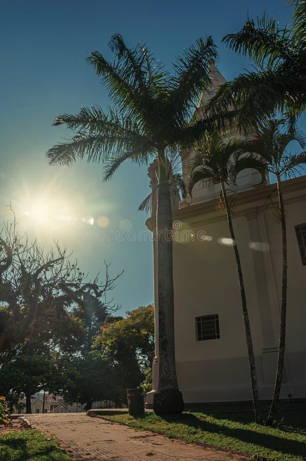 Detaljen av den kyrkliga sidan med kyrktorn, palmträd och evergreen arbeta i trädgården, i en ljus solig dag på São Manuel royaltyfria foton