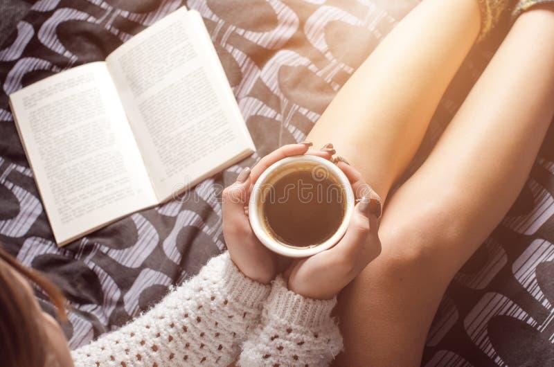 Detaljen av den sexiga unga kvinnan och solen tänder Kvinnauppehälle per kaffekoppen och läst en bok arkivfoto