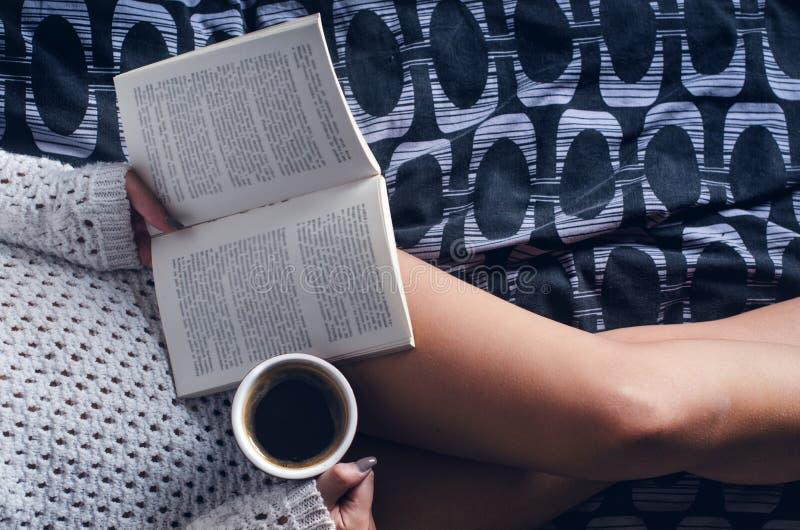 Detaljen av den sexiga unga kvinnan och solen tänder Kvinnauppehälle per kaffekoppen och läst en bok fotografering för bildbyråer