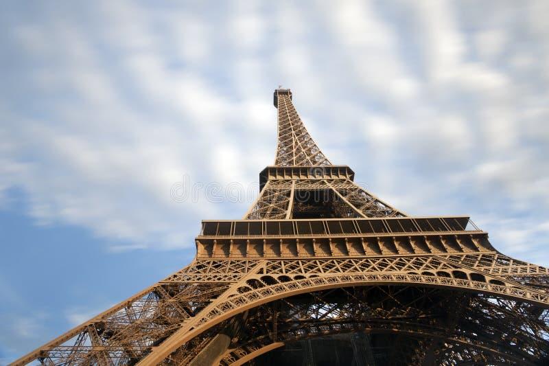 Detaljen av Eiffeltorn med flyttning fördunklar på blå himmel i Paris fotografering för bildbyråer