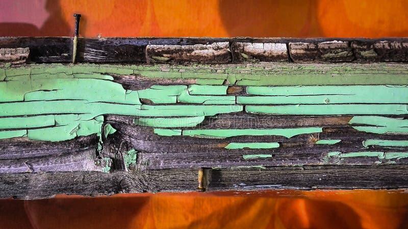 Detaljen av en gammal träfönsterram med skalningsgräsplanmålarfärg, skuggor och spikar på en solig dag royaltyfri foto