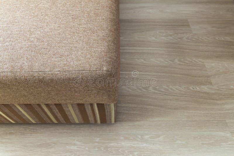 Detaljen av en modern beiga texturerade soffan i vardagsrum på trä royaltyfri bild