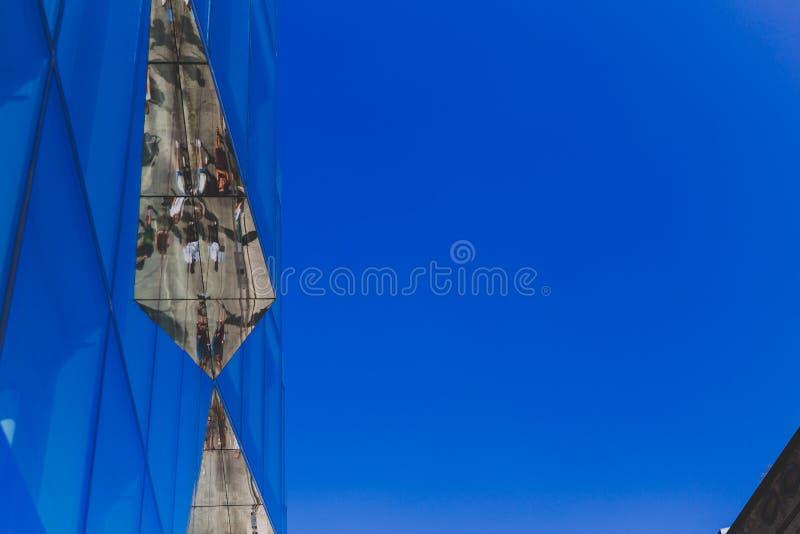 Detaljen av glass byggnad i Dublin stadsmitt i konungen Street med gångare reflekterade på den arkivbild