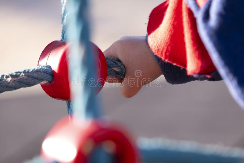 Detaljen av handen av en årig pojke som två spelar i ett utomhus-, parkerar på en solig vinterdag arkivfoton