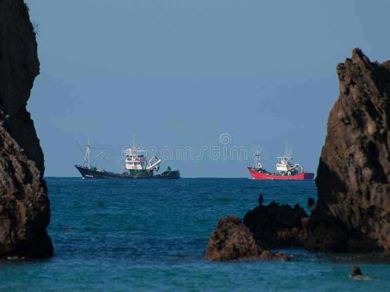 Detaljen av två fiskebåtar mellan stora två vaggar royaltyfri fotografi