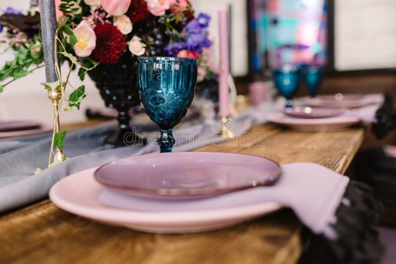 Detaljer av att dekorera av ett bröllop: stearinljus, blommor och ljusstakar royaltyfri foto