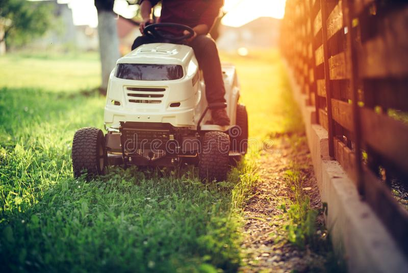 Detaljer av att landskap och att arbeta i trädgården Arbetare som rider den industriella gräsklipparen fotografering för bildbyråer