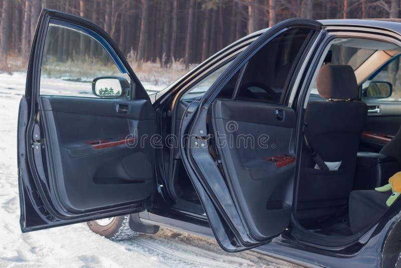 Detaljer av den svarta bilen i kabinen, styrninghjulet, stammen, hastighetsmätaren och de öppna dörrarna royaltyfri foto
