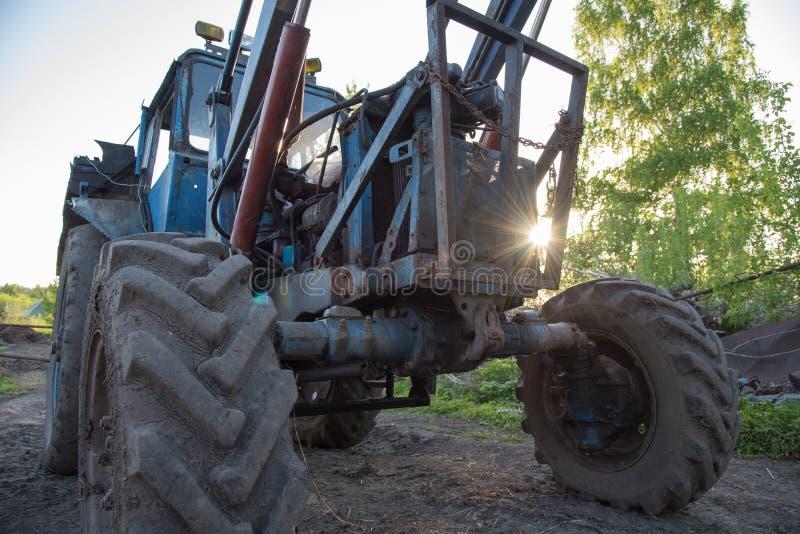 Detaljer av en blå bytraktor med smutsiga hjul, motor, rud royaltyfri foto