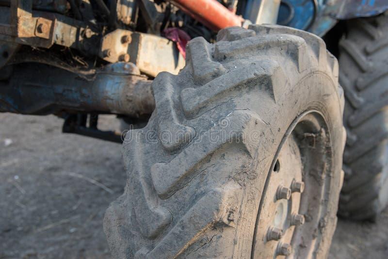 Detaljer av en blå bytraktor med smutsiga hjul, motor, rud royaltyfria foton
