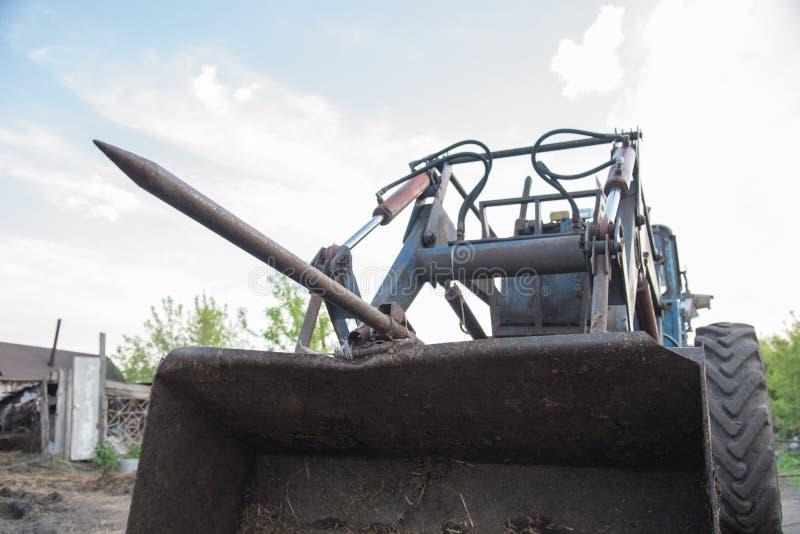 Detaljer av en blå bytraktor med smutsiga hjul, motor, rud arkivbild