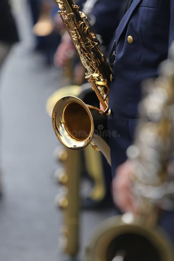 Detaljer av en man som rymmer en saxofon royaltyfri foto
