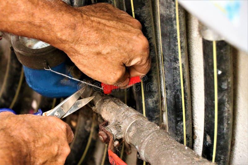 Detaljer av en r?rmokareavsikt p? att reparera en hydraulisk ventil royaltyfri foto