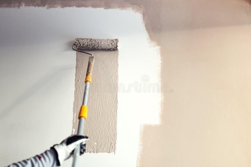 Detaljer av målningväggar, industriarbetare som använder rullen och andra hjälpmedel för att måla väggar arkivbilder