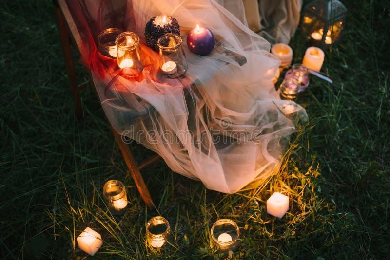 Detaljer för bröllop för nattkonst utomhus-: sommar eller vårceremoni med lowlight stearinljus för dekor som står på täckt stol royaltyfri bild