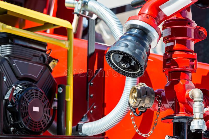 Detaljer för brandlastbil i solljus med slangar och ventiler royaltyfri foto