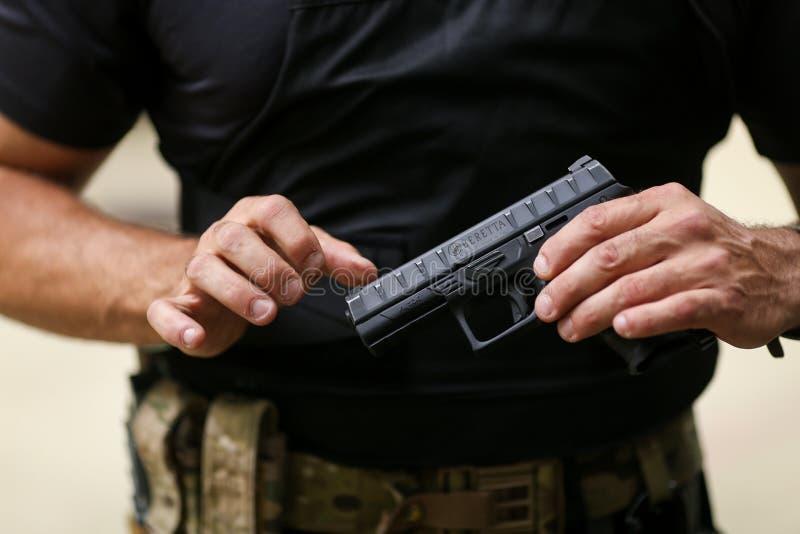 Detaljer med händerna av en soldat som behandlar en pistol för 9mm kaliberBeretta PX4 storm royaltyfri bild