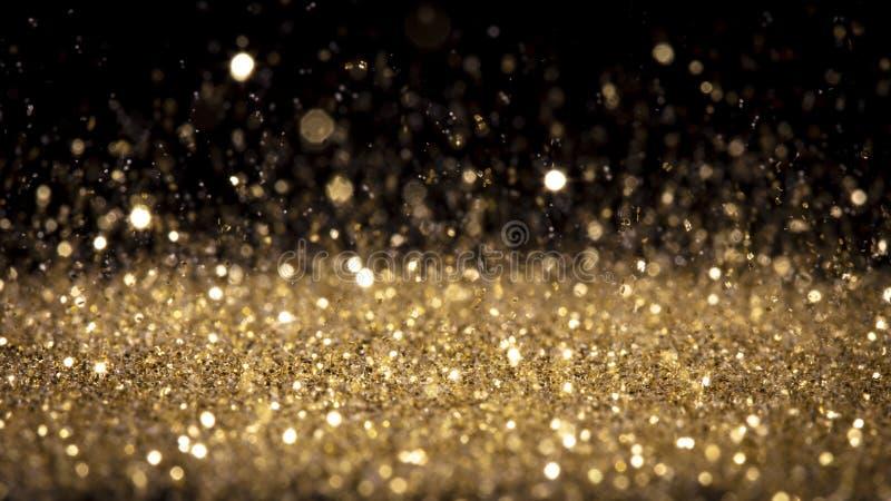 Detaljer om glittring av gulddamm i rörelse arkivfoton
