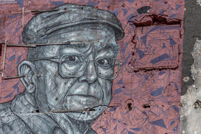 Detaljerad sikt av konstverk som målar på den yttre väggen av byggnad, med illustrationen av äldre man som mycket är uttrycksfull arkivbild