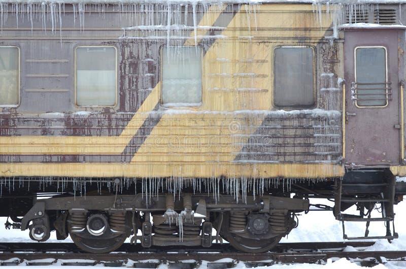Detaljerat foto av ett djupfryst bilpassageraredrev med istappar och is på dess yttersida Järnväg i den kalla vinterseasoen arkivbild