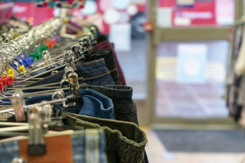 Detaljfoto - byxan och jeans på hängare i välgörenhetsparsamhet shoppar arkivfoto