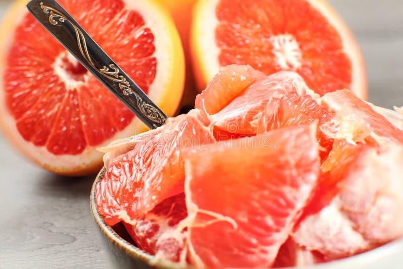Detaljfoto - skalat grapefruktsnitt in i stycken i liten bunke w arkivfoton