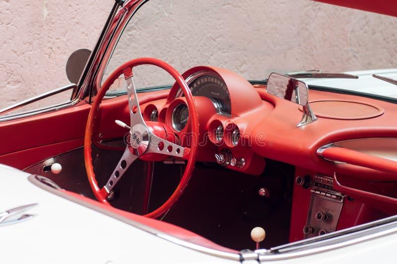 Detaljhandel av den röda instrumentbrädan av den vita Chevrolet Corvette cabrioleten från sextio som parkeras i gatan royaltyfri fotografi