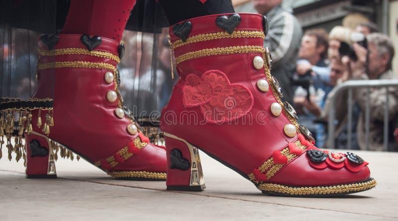 Detaljhandel av röda skor kostymerade kvinnan med den röda klänningen på det Venetian ståtar i Riquewihr i Alsace royaltyfria foton