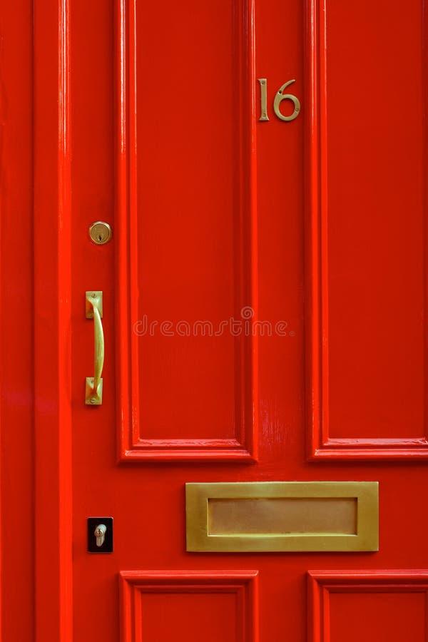 Detaljnärbild av en ljus röd dörr i London England royaltyfria foton